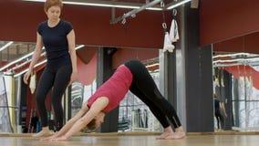 Joga nauczyciel jest w praktyce z młodą kobietą w nowożytnym studiu zbiory