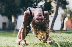 Joga - outdoors młody piękny nikły kobiety joga instruktor robi wielbłądziemu pozy Ustrasana asana ćwiczeniu outdoors zdjęcie stock
