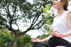 Joga outdoors publicznie parkuje Azjatycka kobieta siedzi w lotosowej pozyci Obrazy Stock