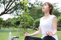 Joga outdoors publicznie parkuje Azjatycka kobieta siedzi w lotosowej pozyci Obrazy Royalty Free