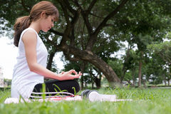 Joga outdoors publicznie parkuje Azjatycka kobieta siedzi w lotosowej pozyci Fotografia Stock