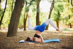 Joga outdoors - sporty dysponowana kobieta robi joga w jesień lesie tła plamy kwiat spojrzenie lubi spojrzenia s Zdjęcia Stock
