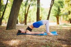 Joga outdoors - sporty dysponowana kobieta robi joga w jesień lesie tła plamy kwiat spojrzenie lubi spojrzenia s Zdjęcia Royalty Free