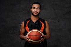 Jogador de basquetebol afro-americano de sorriso no sportswear isolado sobre o fundo escuro foto de stock royalty free