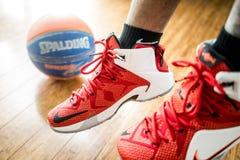 Jogador de basquetebol em instrutores vermelhos Foto de Stock Royalty Free