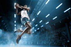Jogador de basquetebol na arena profissional grande durante o jogo Jogador de basquetebol que faz o afundanço Imagens de Stock Royalty Free