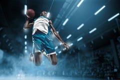 Jogador de basquetebol na arena profissional grande durante o jogo Jogador de basquetebol que faz o afundanço Imagens de Stock