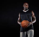 Jogador de basquetebol preto com a bola que olha afastado imagem de stock royalty free