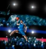 Jogador de basquetebol que faz o afundanço na arena do basquetebol Fotos de Stock