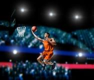 Jogador de basquetebol que faz o afundanço na arena do basquetebol Fotos de Stock Royalty Free