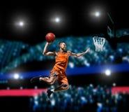 Jogador de basquetebol que faz o afundanço na arena do basquetebol Fotografia de Stock