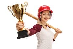 Jogador de beisebol fêmea que guarda um bastão e um troféu do ouro Foto de Stock