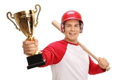 Jogador de beisebol feliz que guarda um bastão e um troféu do ouro Fotografia de Stock
