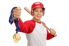 Jogador de beisebol que guarda medalhas de ouro e um bastão Fotografia de Stock Royalty Free