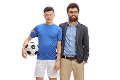 Jogador de futebol adolescente com seu levantamento do pai fotos de stock royalty free