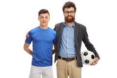 Jogador de futebol adolescente com seu pai fotografia de stock royalty free