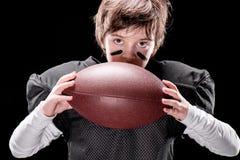 Jogador de futebol americano do menino no sportswear protetor que guarda a bola de rugby foto de stock royalty free