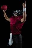 Jogador de futebol americano que levanta as mãos que mantêm uma bola alta em uma mão Imagens de Stock