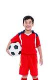 Jogador de futebol asiático novo com futebol que sorri e que guarda o futebol Fotos de Stock