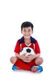 Jogador de futebol asiático novo com futebol que sorri e que guarda o futebol Foto de Stock Royalty Free