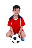 Jogador de futebol asiático novo com futebol que sorri e que guarda o socc Foto de Stock Royalty Free