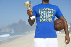 Jogador de futebol brasileiro do campeão que guarda o troféu e a bola de futebol fotografia de stock