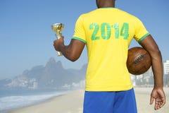 Jogador de futebol brasileiro do campeão que guarda o troféu e o futebol fotografia de stock royalty free