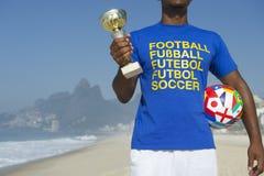 Jogador de futebol brasileiro do campeão que guarda o troféu e o futebol foto de stock royalty free