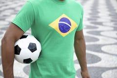 Jogador de futebol brasileiro na camisa da bandeira de Brasil que guarda o Rio do futebol Foto de Stock Royalty Free