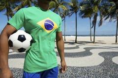 Jogador de futebol brasileiro na camisa da bandeira de Brasil que guarda o Rio do futebol Fotografia de Stock