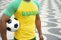 Jogador de futebol brasileiro na camisa de Brasil que guarda o Rio do futebol imagens de stock