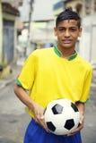Jogador de futebol brasileiro novo que guarda a bola de futebol na rua fotografia de stock royalty free