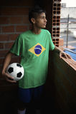 Jogador de futebol brasileiro novo sério que olha para fora a janela de Favela Foto de Stock