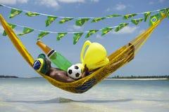 Jogador de futebol brasileiro que comemora com Champagne e troféu fotografia de stock