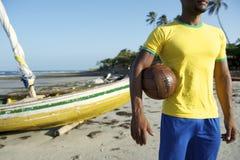 Jogador de futebol brasileiro que guarda a praia de Nordeste da bola de futebol imagem de stock royalty free