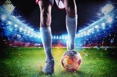 Jogador de futebol com soccerball no fogo no estádio durante o fósforo foto de stock