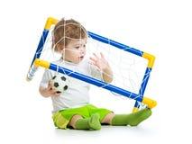Jogador de futebol da criança que guarda a bola de futebol Fotografia de Stock Royalty Free