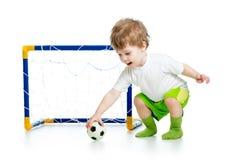 Jogador de futebol da criança que guarda a bola de futebol Fotos de Stock Royalty Free