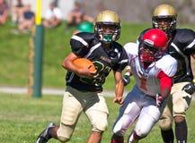 Jogador de futebol da High School que corre com a bola Fotografia de Stock