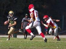 Jogador de futebol da High School que corre com a bola Imagens de Stock