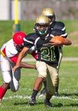 Jogador de futebol da High School que corre com a bola Imagens de Stock Royalty Free