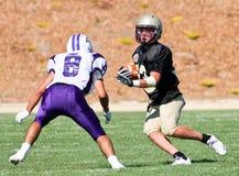Jogador de futebol da High School que corre com a bola durante um jogo Foto de Stock