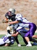 Jogador de futebol da High School que está sendo abordado durante um jogo Fotografia de Stock Royalty Free