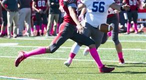 Jogador de futebol da High School que punting a bola durante um jogo Imagem de Stock Royalty Free