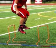 Jogador de futebol da High School que salta sobre mini obstáculos Fotos de Stock Royalty Free
