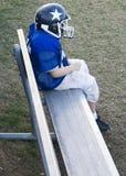 Jogador de futebol da juventude sozinho no banco Fotografia de Stock Royalty Free