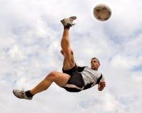 Jogador de futebol em um retrocesso de bicicleta Fotografia de Stock Royalty Free