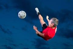 Jogador de futebol em um retrocesso de bicicleta Fotos de Stock