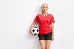 Jogador de futebol fêmea novo em um jérsei vermelho fotos de stock royalty free