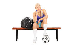 Jogador de futebol fêmea preocupado que senta-se em um banco Fotografia de Stock Royalty Free